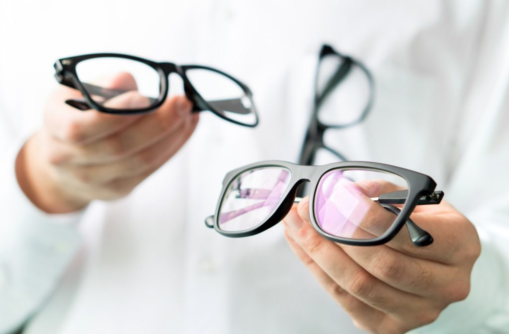 Optician comparing lenses and showing a customer different options in spectacles