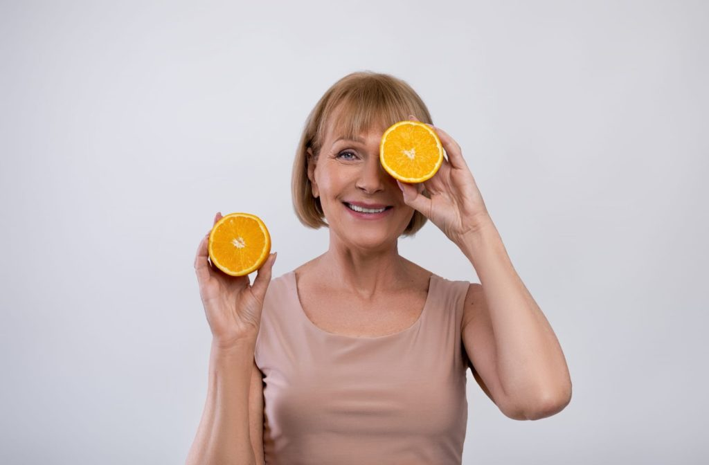A smiling elderly woman holding orange's in front of her eye's showing that Vitamin C boosts eye health