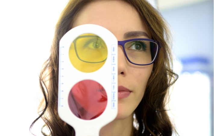 A woman completing a colour blindness test as part of the eye exam performed by her optometrist